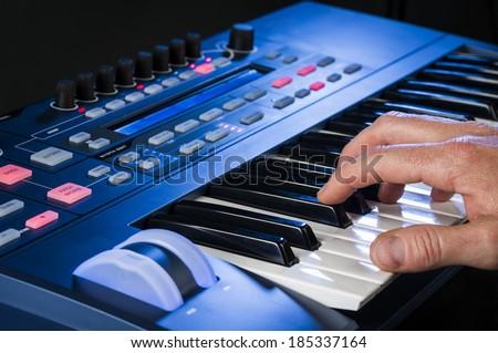 a man playing music on a keyboard - stock photo