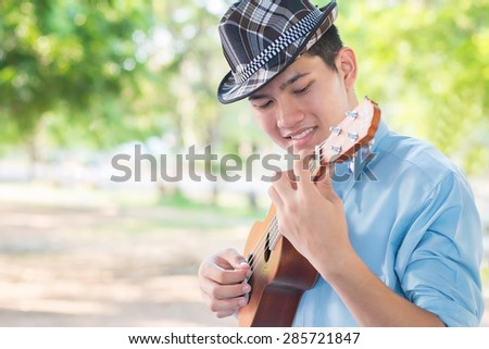 A man playing ukulele so happiness in park.