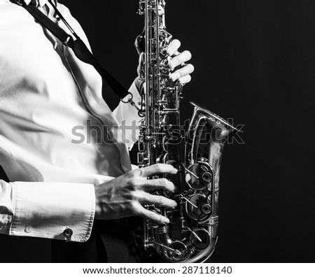 A man plays the saxophone close up. - stock photo
