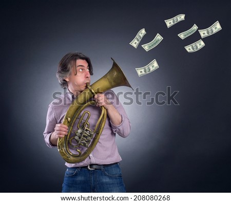 A man plays the trumpet blowing out her money. - stock photo