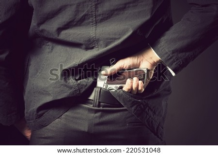 A man, policeman or gangster concealing his gun behind his back - stock photo