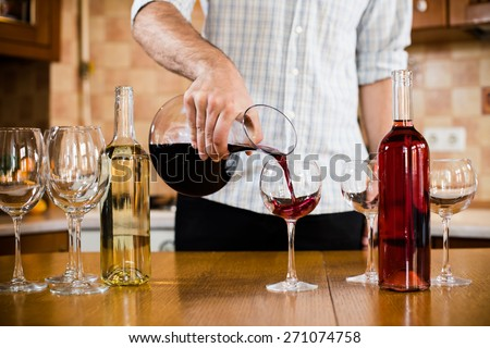 A man pours red wine from the decanter into a glass, home kitchen interior - stock photo