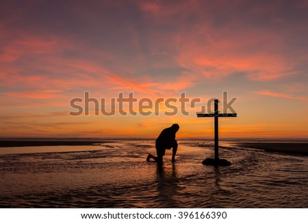 A man praying by a black cross with a flowing stream water around it, at a beach with the sunset sky. - stock photo