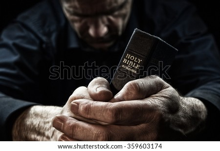 A Man praying holding a Holy Bible. - stock photo