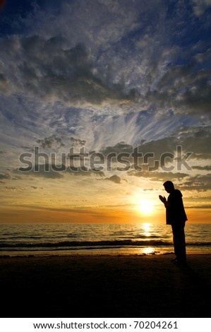A man praying on the beach in front of a beautifully unique sunset. - stock photo