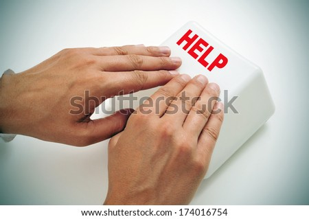 a man pressing a giant help key with his hands - stock photo