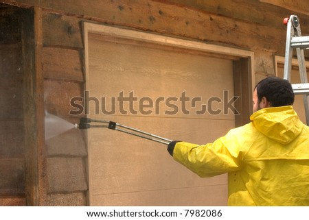 a man pressure washing a wood sided garage - stock photo