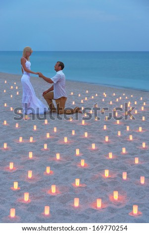A man propose marriage to woman at sea beach in many candle lights against sunset- St.Valentines Day romantic concept - stock photo