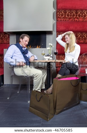 A man proposing to a woman in front of a restaurant fireplace - stock photo