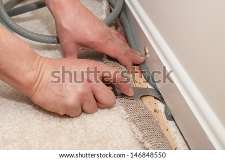 A man pulls back carpet in order to install insulation under the molding. - stock photo