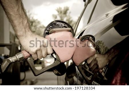 A man pumping gas into his gas tank. - stock photo