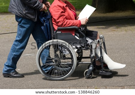 A man pushing a woman in a wheelchair with a injured leg - stock photo
