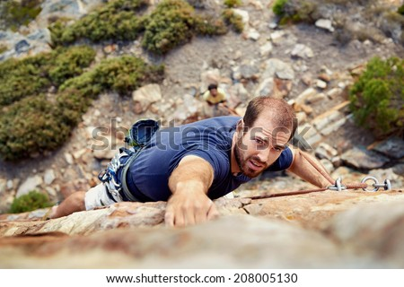 A man reaching for a grip while he rock climbs on a steep cliff - stock photo