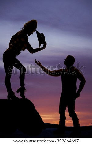 a man reaching up to his cowgirl offering her help down off the cliff.