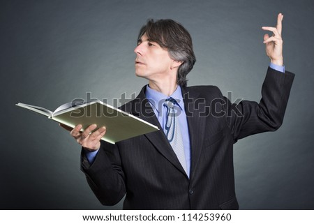 A man reads a book emotionally gesticulating. - stock photo