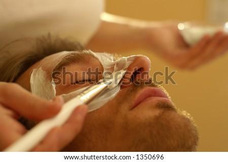 A man receives a facemask treatment in the beautyfarm - stock photo
