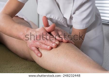 A man receiving a ayurvedic massage on his legs - stock photo