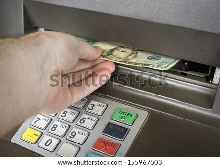 a man receiving money from the ATM.