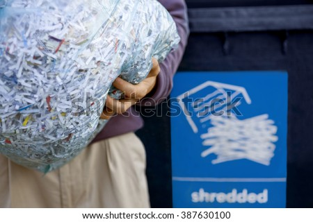 A man recycling a bag of shredded paper - stock photo