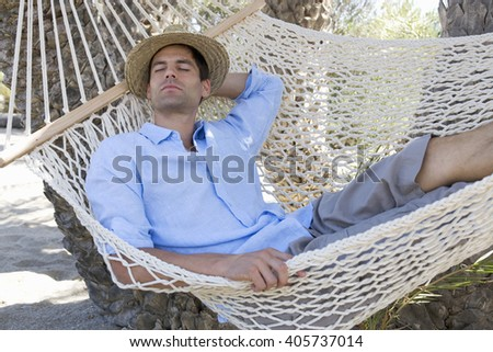 A man relaxing in a hammock - stock photo