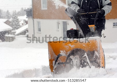 A Man Removes Snow In Winter. A Man Clears Snow With A Snow Cutter