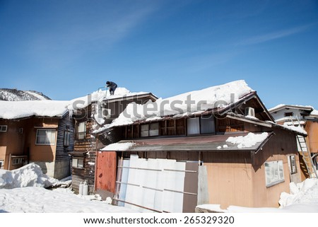 A man removes snow on the roof of the Japanese house in Takayama, Japan - stock photo
