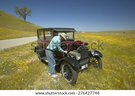 A man repairing his maroon Model T, surrounded by spring flowers off of Route 58, Shell Road, CA