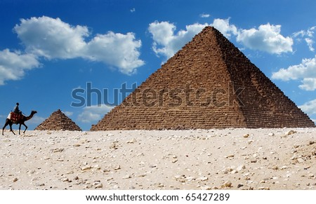 A man riding a camel walks past the iconic pyramids of Giza in Egypt - stock photo