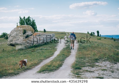 A man running away from a dog - stock photo