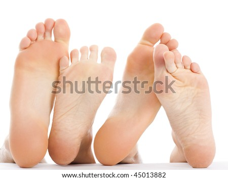 A man 's and a woman 's feet in an abstract composition, expressing love, friendship, a warm relationship isolated on white.