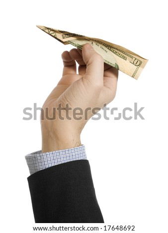 A man's hand about to throw a paper plane made of a ten dollar bill. - stock photo