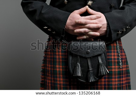 A man's hand clasped over a Scottish kilt and purse. - stock photo