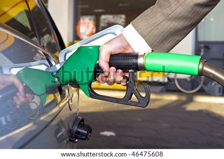 A man's hand filling up a car with gas or petrol at a gas station. - stock photo