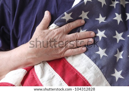 a man's hand on a USA flag against his chest - stock photo