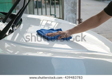 A man's hand wipe the car with microfiber cloth. Cleaning the car. Wipe off water.