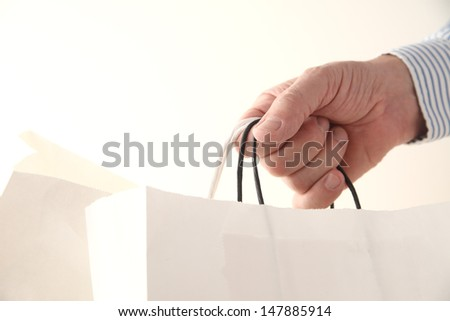a man's hand with two store paper bags - stock photo