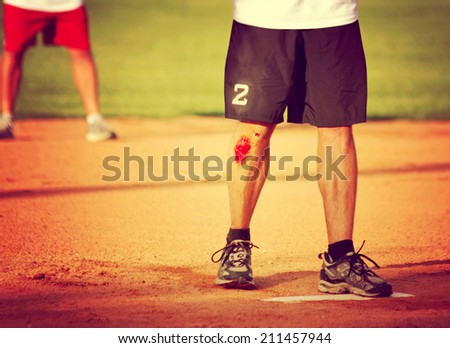 a man's legs on a baseball or softball field with a big scrape toned with a retro vintage instagram filter  - stock photo