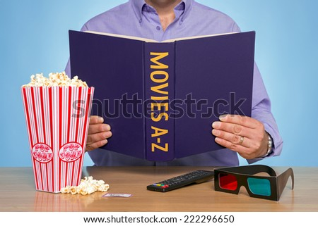 A man sat at a table reading a MOVIES A-Z book - stock photo