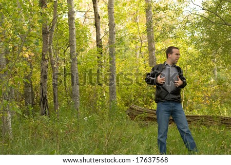 A man scratching his body because he got poison ivy through his shirt - stock photo