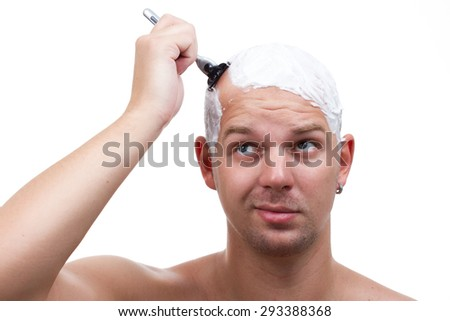 a man shaves his head thoughtfully - stock photo