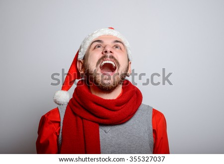 A man shouts with joy. Happy Businessman wearing a Santa hat on New Year's corporate parties. Studio photo, isolated on a gray background