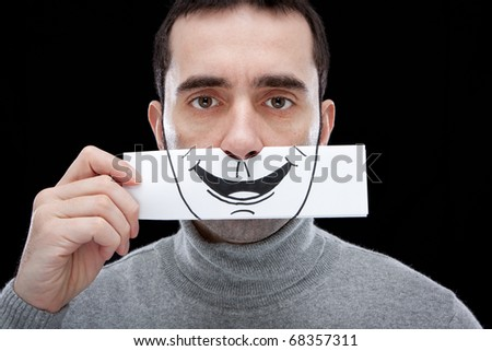 A man showing a blank, indifferent expression, holding a paper with a smile drawn on it in front of his face. - stock photo