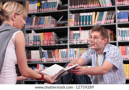 a man showing a page in the book to the woman - stock photo