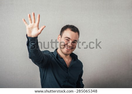 A man shows his hand hello. On a gray background. - stock photo