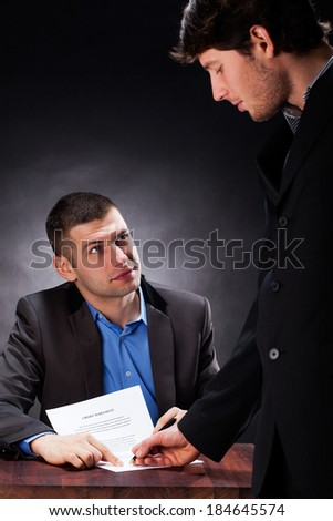 A man signing a credit agreement with a lawyer - stock photo