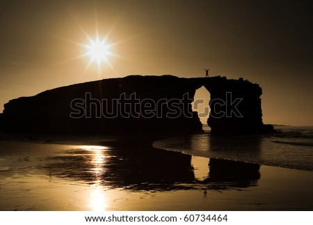 A man silhouette over a big rock in a beach at sunset. Reflection of the rock is clearly visible on the sand. - stock photo