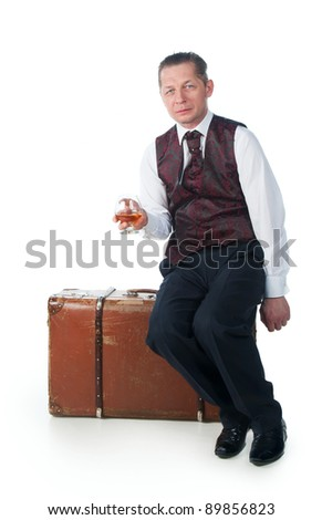 A man sits on a suitcase on a white background
