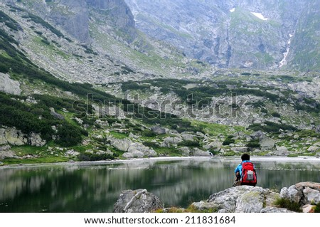A man sits on the stone and looks at the glacial Fish Lake in the Seven Lakes National Park in Bulgaria - stock photo