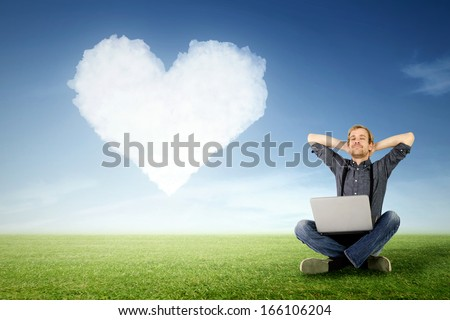 a man sits relaxed with laptop on the meadow with a cloud in heart shape in the background - stock photo