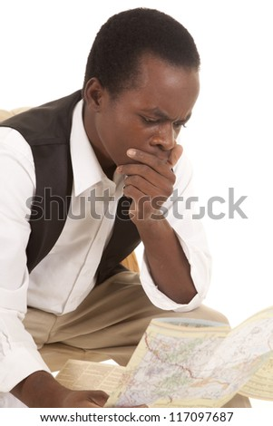 A man sitting and looking at a map with a shocked or confused expression on his face
